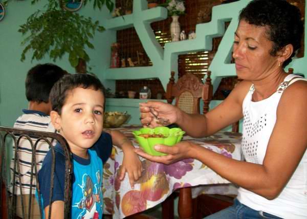 Niño cubano se alimenta con su madre. Foto Abel Rojas.
